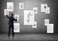 Businessman putting up business posters with sketches on concrete wall Royalty Free Stock Photography