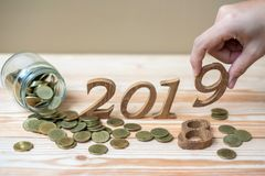 "businessman putting ""2019"" wooden number with gold coins stack on wooden table stock images"
