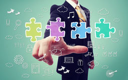 Businessman with puzzle and business cartoon. Businessman pointing a piece of the puzzle with business concept cartoon Stock Photo