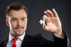 Businessman with puzzle element. Confident young man holding puzzle element while standing isolated on black Stock Image