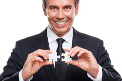 Businessman with puzzle elements. Portrait of confident mature man in formalwear holding two puzzle elements and smiling while standing against white background Royalty Free Stock Photo