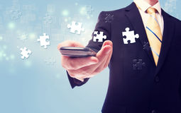 Businessman with puzzle over cellphone Royalty Free Stock Photos