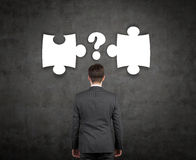 Businessman with puzzle. And question mark over head Stock Images