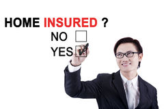 Businessman with question of home insured. Young businessman using a pen while selecting a yes option with a question of home insured on the whiteboard Royalty Free Stock Image