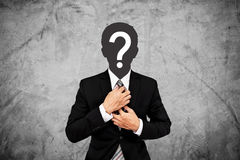 Businessman with question mark on head, on concrete wall background Royalty Free Stock Image