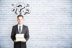 Education and inquiry concept. Businessman with question marks holding books on white brick wall background with copy space. Education and inquiry concept Stock Photos