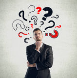 Businessman with question marks Stock Photography