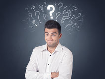 Businessman with question marks. Young casual businessman with white question marks above his head Stock Image