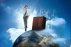 Businessman racing on top of the world beside server. In cloudy blue sky stock photography