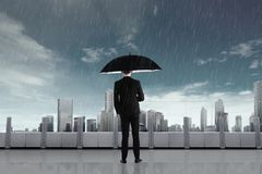Businessman in the rain with umbrella Stock Photos