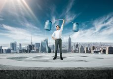 Businessman raises bar of bottles with water. Purposeful and confident businessman raises a bar of bottles with water, cityscape on background. Succuss business Stock Images