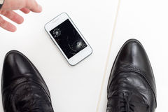 Businessman raises his broken smartphone Royalty Free Stock Images