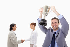 Businessman raising cup with hand shaking colleagues behind him Royalty Free Stock Images