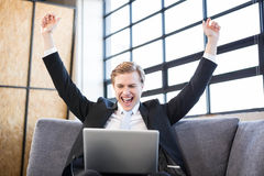 Businessman raising hands with excitement in front of laptop Royalty Free Stock Images