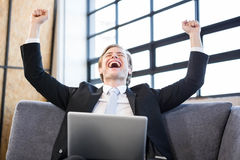Businessman raising hands with excitement in front of laptop Stock Photo