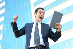 Businessman raising his arm while looking at tablet computer Stock Photos