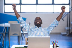 Businessman raising his arms front of laptop Royalty Free Stock Photos