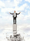 Businessman raising his hands to heaven standing on crumbling column Royalty Free Stock Photos