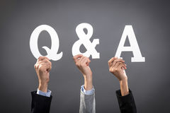 Businessman raising their hands with letters showing Q & A sign Stock Photo