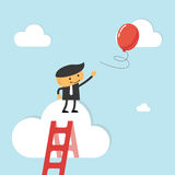Businessman reach out for balloon. Concept of funny and light reaching goals Stock Image