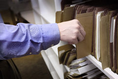 Businessman Reaching Hand for Files on Shelf Stock Photography