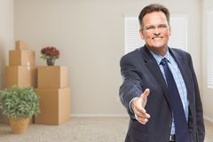 Businessman Reaching for Hand Shake in Room with Packed Boxes Royalty Free Stock Photo