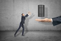 Businessman reaching out to a black metal barrel over a big hand on grey background royalty free stock photography