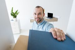 Businessman reaching for paperwork on shelf. Smiling young businessman reaching to take binders with paperwork off the shelf at office Stock Image