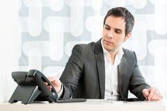 Businessman reaching for the telephone Royalty Free Stock Image