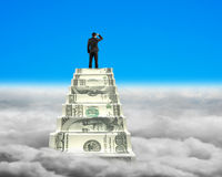Businessman reaching the top of money stairs with sky cloudscape Royalty Free Stock Images