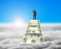Businessman reaching the top of money stairs with sunlight cloud Stock Image