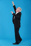 Businessman reaching upwards Stock Photo