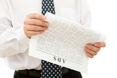 Businessman reading ads from paper Stock Images