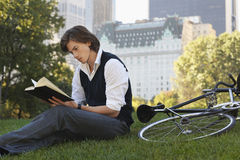 Businessman Reading Book By Bicycle In Park Stock Images
