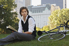 Businessman Reading Book By Bicycle In Park Stock Photo