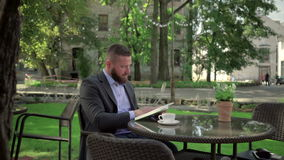 Businessman reading book during coffe break. Outdoor. Steadicam shot. He is young and has beard. He is dressed on shirt and jacket. At backgroung there is stock footage