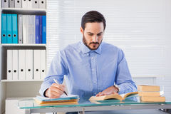 Businessman reading book while writing at his desk Royalty Free Stock Image