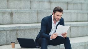 Businessman reading business papers on street. Man sitting on stairs