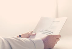 Businessman reading a business report. Close up of a businessman reading a business report Stock Images