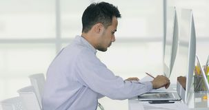 Businessman reading chart and graph. Young and handsome businessman reading business chart and graph and typing computer keyboard in modern office stock video footage