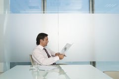 Businessman Reading Document At Conference Table Stock Photos