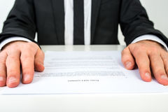Businessman reading a document with focus to the text Terms and. Close up low angle view of the hands of a businessman reading a document or contract resting on royalty free stock photos