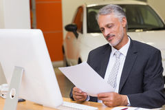 Businessman reading document at office desk Stock Photo