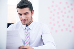 Businessman reading document in office royalty free stock photography