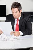 Businessman Reading Document In Office Royalty Free Stock Photo