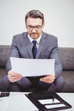 Businessman reading document while sitting on sofa Royalty Free Stock Photo