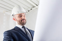 Businessman reading documents at the construction site. Stock Image