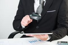 Businessman reading documents with magnifying glass stock photo