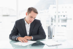 Businessman reading documents at office desk Stock Images