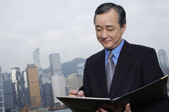 Businessman Reading Documents Outdoors Stock Photography